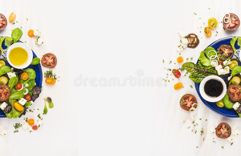 Salad with tomatoes, greens, dressing, oil and feta cheese in blue plate on white wooden background, top view , banner for website royalty free stock photo
