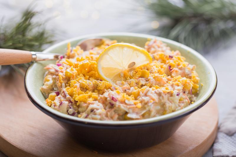 Salad with tuna, corn, onion, raw carrot, eggs, in   gray plate on a light concrete background. New Year salad recipes. Top view royalty free stock photo