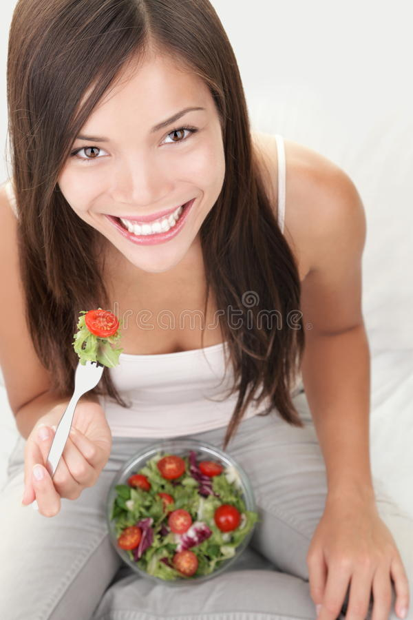 Salad woman eating healthy. Bowl of salad. Asian / Caucasian woman smiling happy looking at camera stock photos