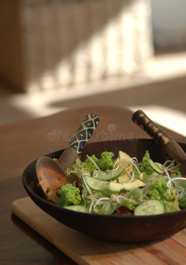 Salad in wooden bowl on table stock photography