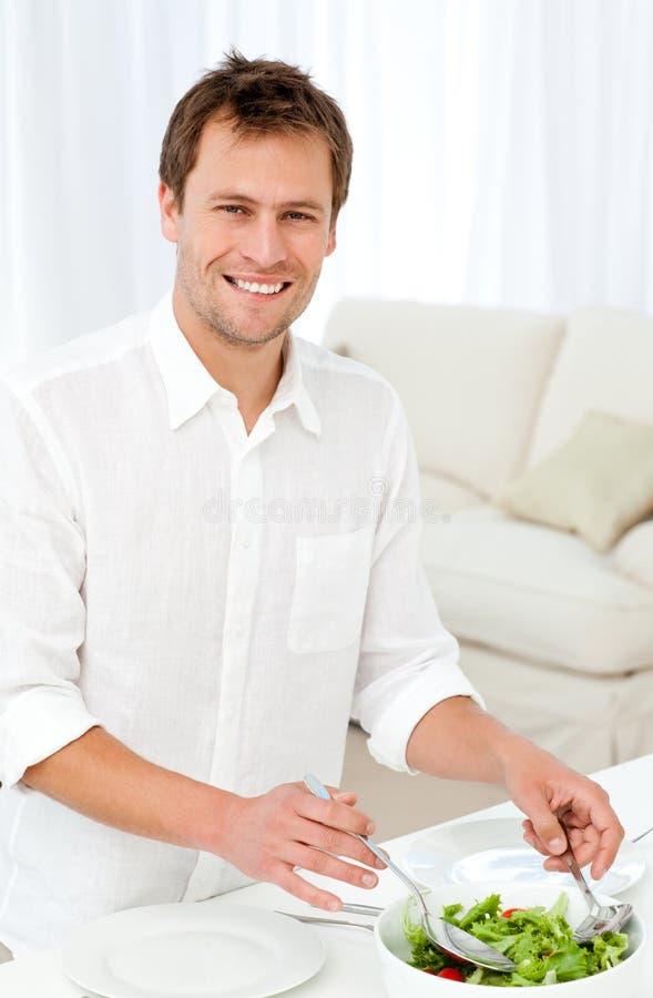 Salada alegre do serviço do homem que está em uma tabela fotografia de stock