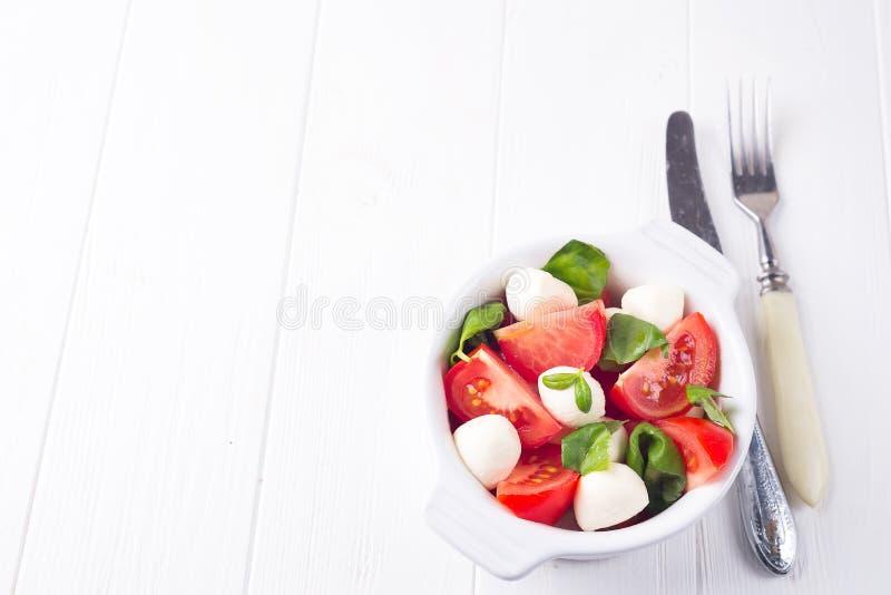 A salada caprese do tomate fresco italiano com os tomates maduros da fatia e as mini bolas do mozzarella com manjericão fresca sa imagem de stock royalty free