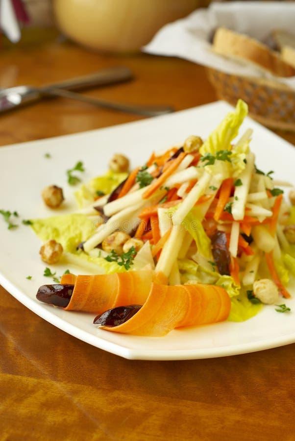 Salada com cenouras, maçãs, tâmaras e avelã fotos de stock royalty free