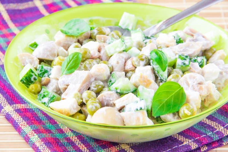 Salada com ervilhas verdes, galinha, cogumelos, pepino e mayonnai imagens de stock royalty free