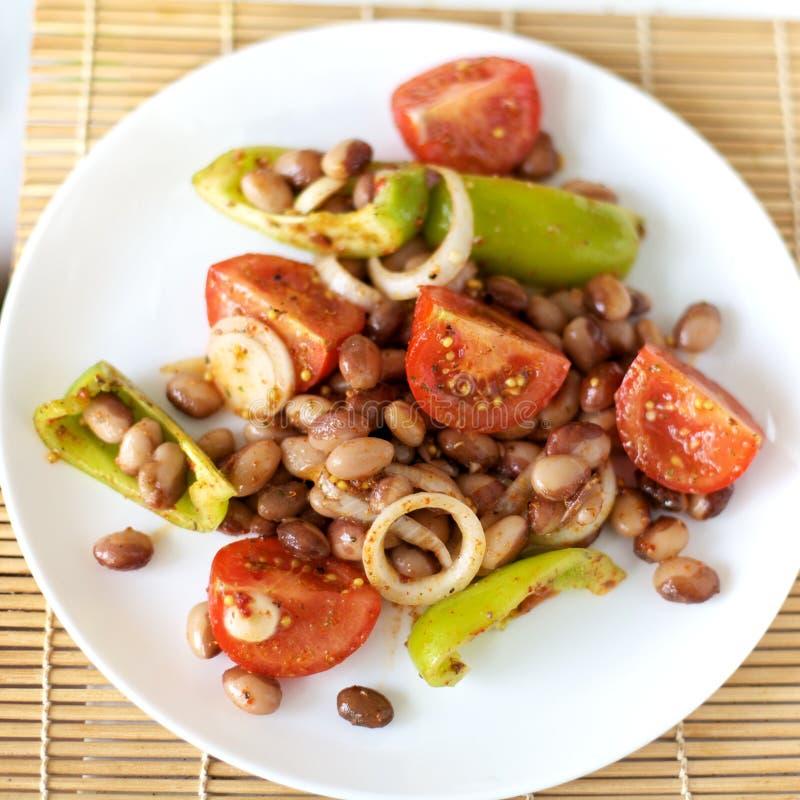 Salada com feijões e vegetais em uma placa branca fotos de stock