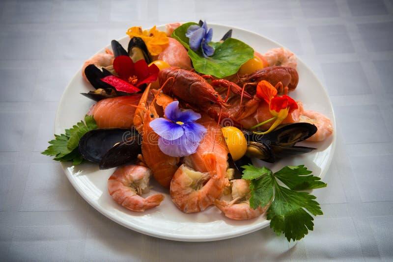 salada com lagostas e camarão fervidos com fruto em uma placa em uma tabela com uma toalha de mesa branca fotografia de stock royalty free
