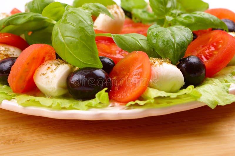 Salada com manjericão, mozzarella, azeitonas e tomate fotografia de stock