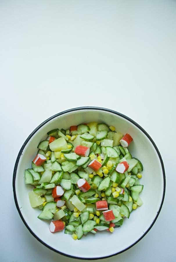 Salada com milho, caranguejos, pepinos em uma taça branca sobre fundo branco Salada vegetal Processo de cozedura foto de stock