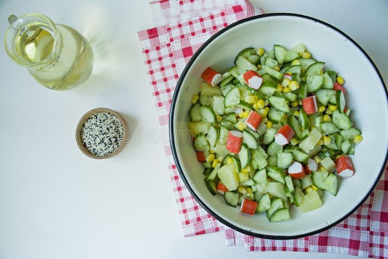 Salada com milho, caranguejos, pepinos em uma taça branca sobre fundo branco Salada vegetal Processo de cozedura imagens de stock royalty free