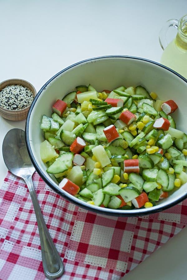 Salada com milho, varas do caranguejo, pepinos em uma bacia branca em um fundo branco Salada do vegetariano Processo de cozimento foto de stock royalty free
