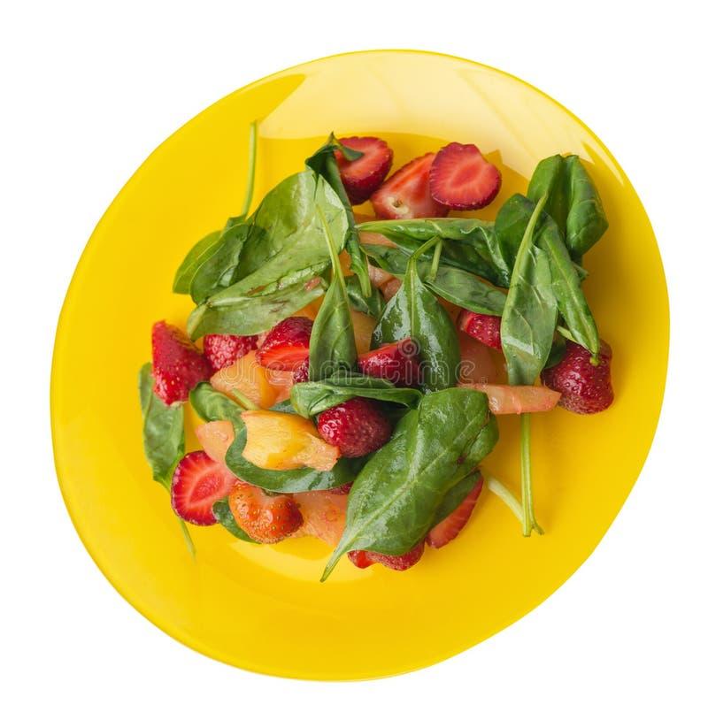 Salada com morangos, abacaxi e espinafres em uma placa salada do vegetariano do fruto isolada na opinião superior do fundo branco imagem de stock royalty free