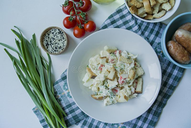 A salada com os biscoitos, as varas do caranguejo, a faixa da galinha, as ervas frescas e o queijo duro temperados com manteiga d imagem de stock