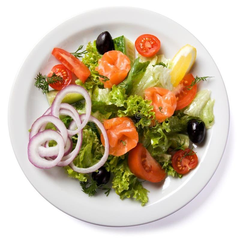 Salada com os salmões seridos na placa branca fotografia de stock