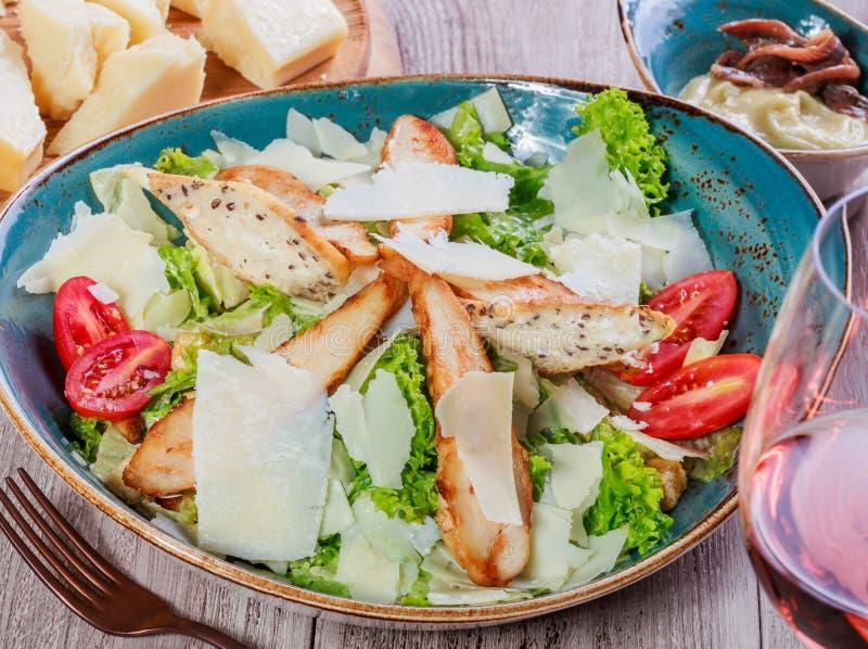 Salada com peito de frango, queijo parmesão, pão torrado, tomates, verdes misturados, alface e vidro do vinho no fundo de madeira foto de stock