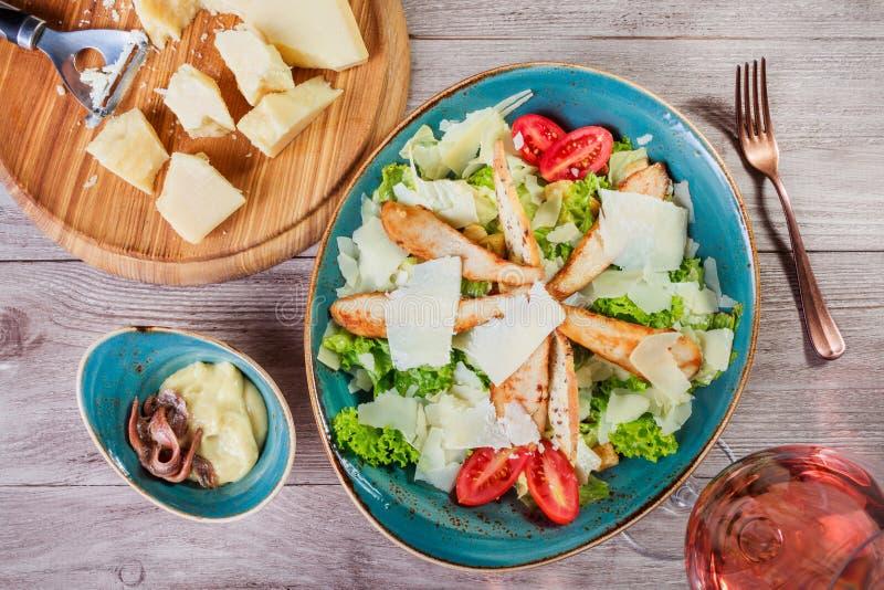 Salada com peito de frango, queijo parmesão, pão torrado, tomates, verdes misturados, alface e vidro do vinho no fundo de madeira imagem de stock