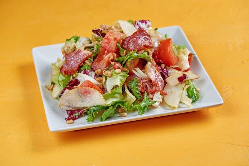 Salada com pera, proshutto, uvas, rúcula, queijo macio e porcas Salada do outono imagens de stock royalty free