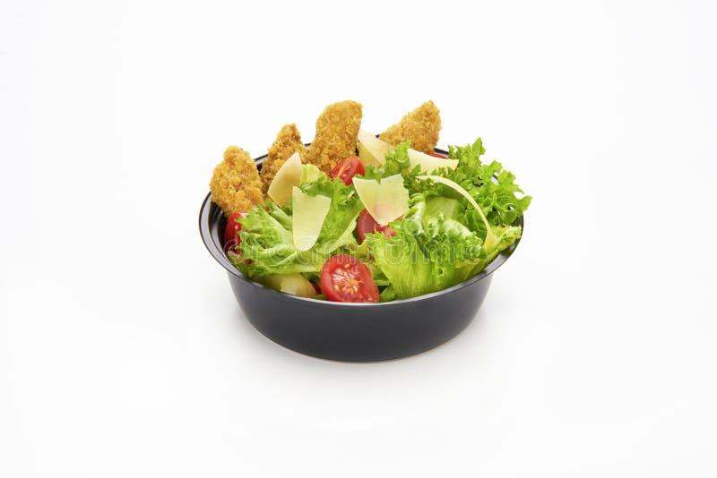 A salada com tiras do frango frito e cortou o queijo parmesão em um plástico leva embora a bacia no fundo branco fotografia de stock
