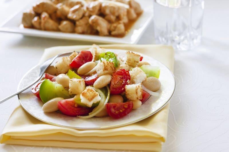Salada com tomates, os feijões brancos fervidos e o pão torrado foto de stock