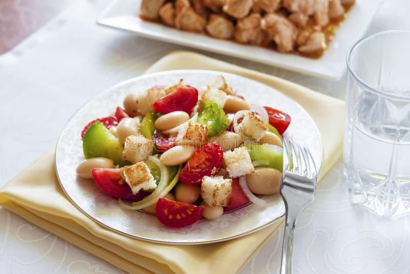 Salada com tomates, os feijões brancos fervidos e o pão torrado imagem de stock royalty free