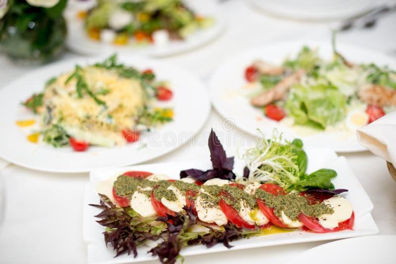 Salada conservada em estoque de Foto Caprese com tomates, manjericão, mussarela, azeitonas e azeite Salada tradicional italiana d imagens de stock royalty free