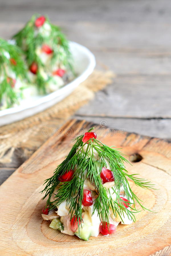 Salada da árvore de Natal em uma placa de madeira Salada festiva deliciosa com carne, cogumelos, pepinos e ovos fotografia de stock royalty free