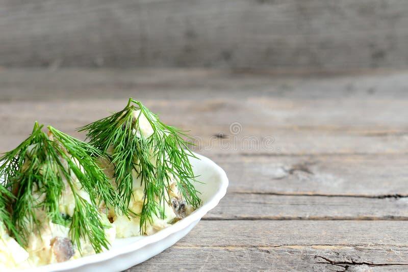 Salada da árvore de Natal em uma placa Salada com a carne, os cogumelos, os pepinos e os ovos decorados com aneto fotos de stock royalty free