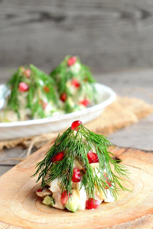 Salada da árvore de Natal Salada com a carne, os cogumelos, os pepinos e os ovos decorados com aneto e romã imagem de stock