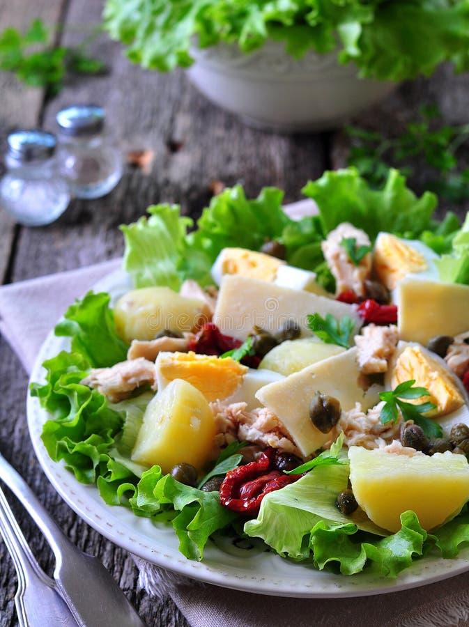 A salada da alface, alface de iceberg, com atum enlatado, secou tomates, batatas fervidas, alcaparras e queijo parmesão, vestidos foto de stock