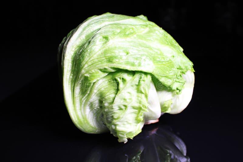 Salada da alface de iceberg Salada verde inteira da alface de iceberg no fundo reflexivo preto do estúdio espelho brilhante preto fotografia de stock royalty free