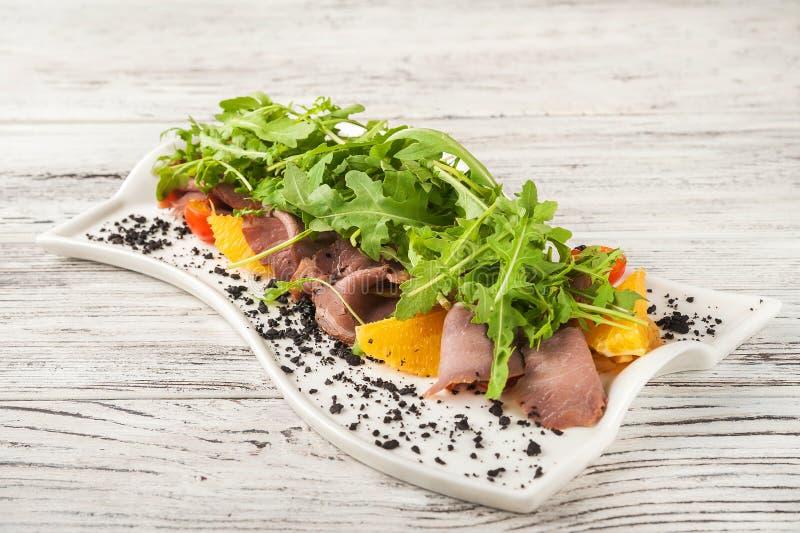 Salada da carne com laranjas e rúcula em um close-up branco da placa Petisco do jamon e rúcula com laranjas em um espaço da cópia fotografia de stock