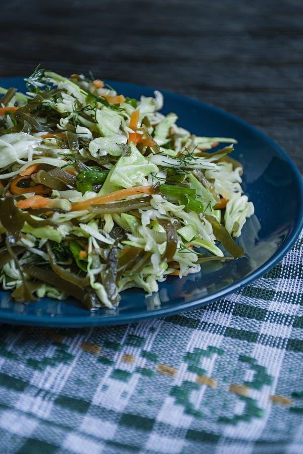 A salada da couve branca, da couve de mar e de cenouras frescas temperou com azeite, aneto e salsa Fundo de madeira escuro imagem de stock