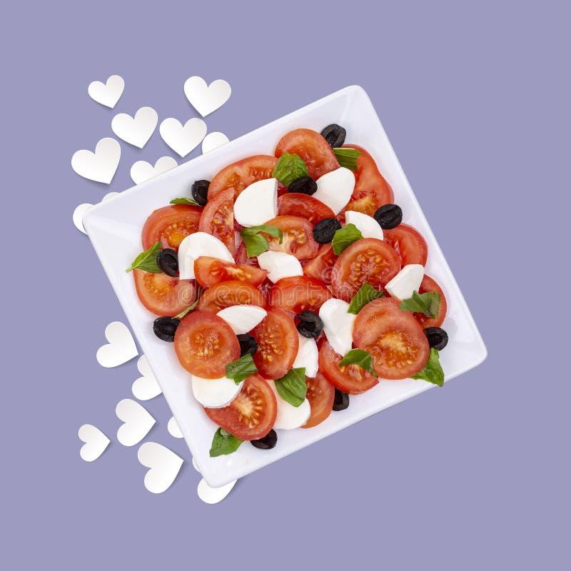 Salada da luz do sol do verão do tomate, da manjericão e da mussarela em um fundo colorido com corações fotos de stock royalty free