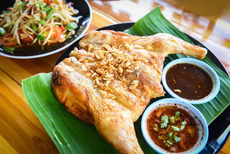 Salada da papaia e galinha grelhada com o molho servido na placa na tabela de madeira - alimento asiático do menu tailandês do tu fotos de stock