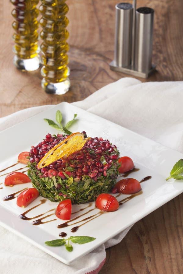Salada da romã com hortelã e tomate e óleo em um fundo de madeira fotos de stock