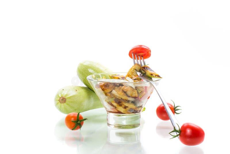Salada de abobrinha grelhada e quente com tomate fresco de cereja e cebolas imagens de stock