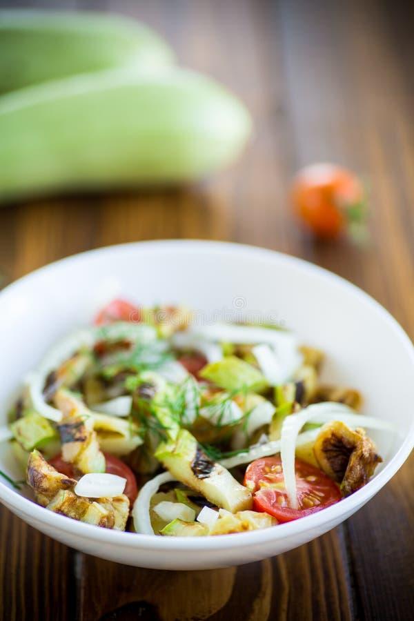 Salada de abobrinha grelhada e quente com tomate fresco de cereja e cebolas foto de stock royalty free