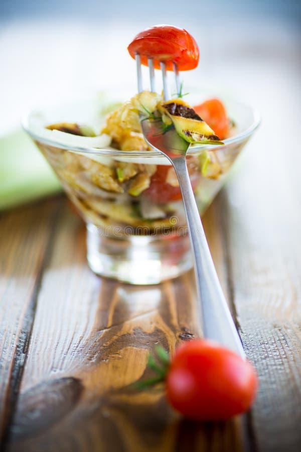 Salada de abobrinha grelhada e quente com tomate fresco de cereja e cebolas fotografia de stock