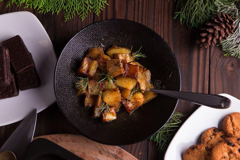 Salada de batata doce sauteed na bacia preta no fundo de madeira marrom Prato lateral para o Natal, a ação de graças, e o ruído d fotografia de stock