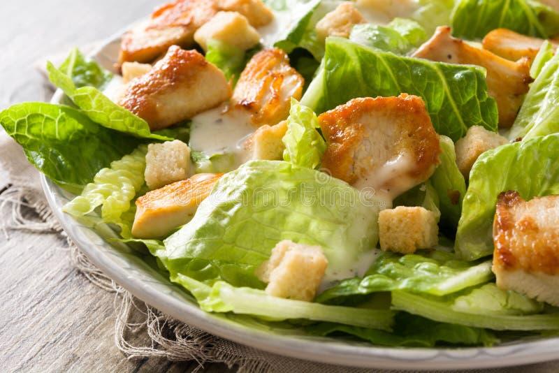 Salada de Caesar com alface, galinha e pão torrado na tabela de madeira imagens de stock royalty free