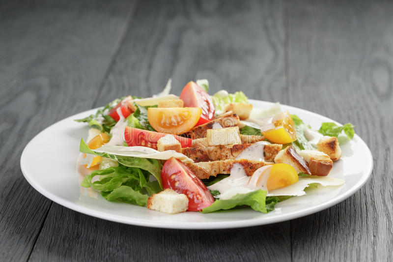 Salada de Caesar com a galinha na tabela de carvalho imagens de stock royalty free