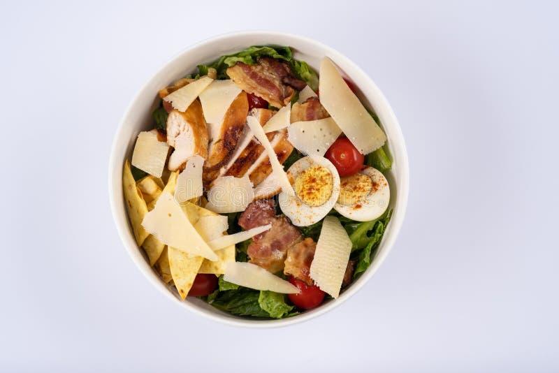 A salada de Caesar do foco seletivo com roasted chiken, bacon, ovos de codorniz, folhas da alface, microplaquetas, Parmesão, toma foto de stock