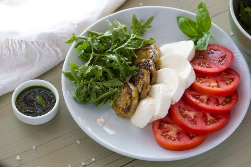 Salada de Caprese com mussarela, tomate, manjericão e beringela grelhada na placa branca Vista superior no fundo fotografia de stock royalty free