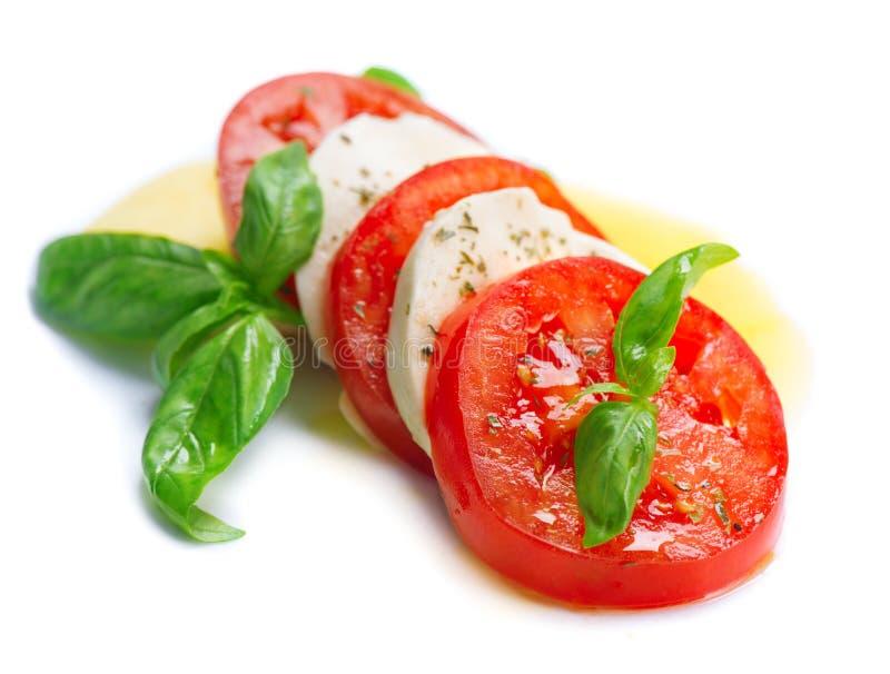 Salada de Caprese Fatias do tomate e da mussarela com manjericão foto de stock royalty free