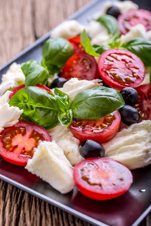 Salada de Caprese Salada mediterrânea Manjericão e azeite dos tomates de cereja da mussarela na tabela de carvalho velha Culinári fotografia de stock royalty free