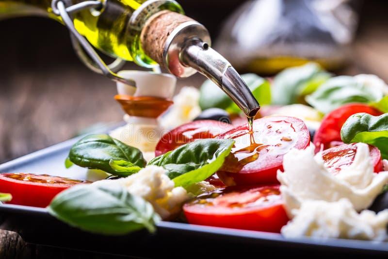 Salada de Caprese Salada mediterrânea Manjericão e azeite dos tomates de cereja da mussarela na tabela de carvalho velha Culinári imagens de stock