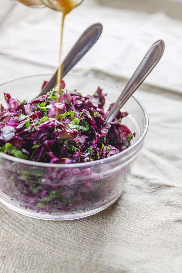 Salada de couve azul fresca com ervas e porcas em uma bacia de vidro em uma toalha de mesa r?stica Derrame sobre o molho Saud?vel fotos de stock