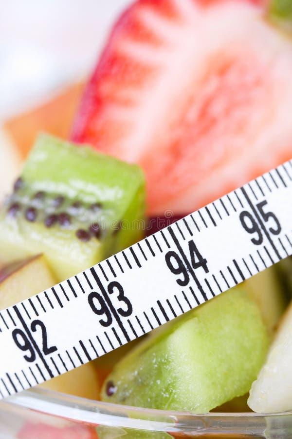 Salada de fruta na placa branca com fita da medida imagem de stock royalty free