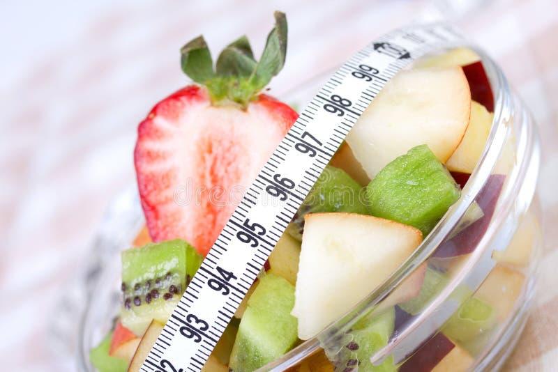 Salada de fruta na placa branca com fita da medida fotos de stock royalty free
