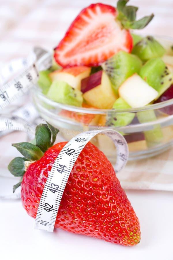 Salada de fruta na placa branca com fita da medida fotografia de stock royalty free