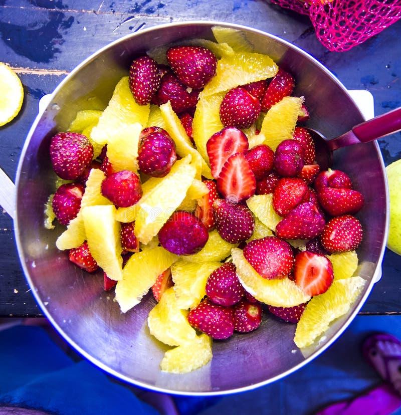 Salada de fruto alaranjada descascada e morangos maduras fotografia de stock royalty free